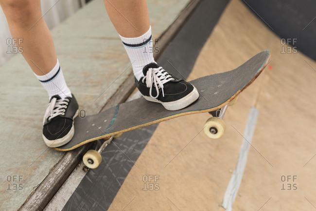 Close-up of female skateboarder skating on skateboard ramp at skateboard court
