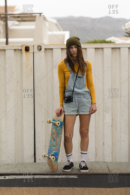 Beautiful female skateboarder standing with skateboard on skateboard ramp