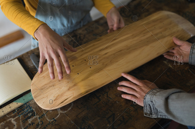 Close-up of skateboarders examining skateboard deck in workshop