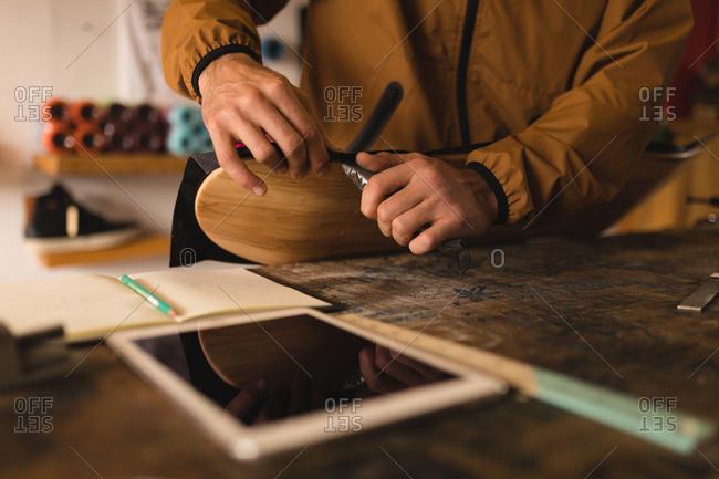 Close-up of man repairing skateboard in workshop