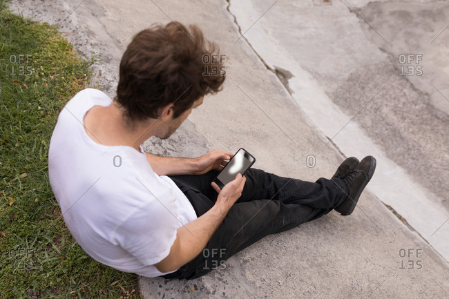 High angle view of man using mobile phone at skateboard park