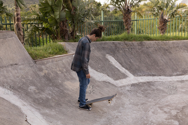 Side view of man standing with skateboard at skateboard park
