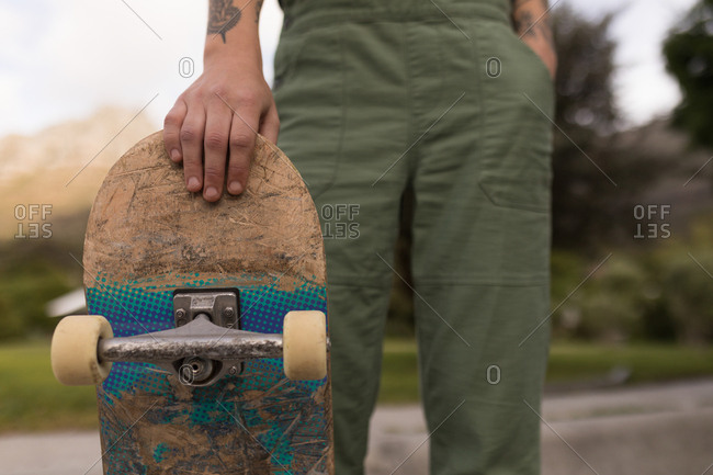 Close-up of woman standing with skateboard at skateboard park