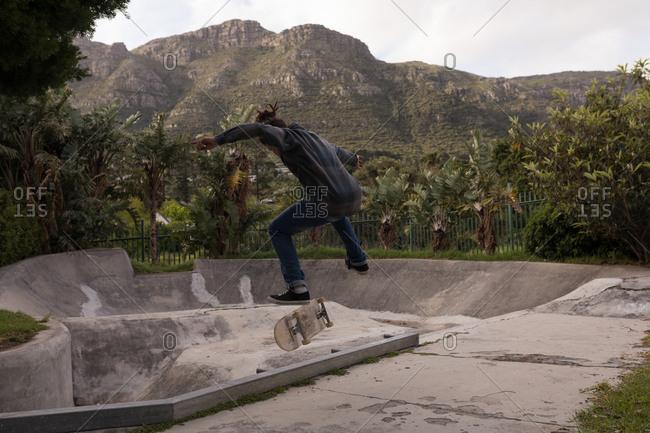 Rear view of man skateboarding at skateboard park