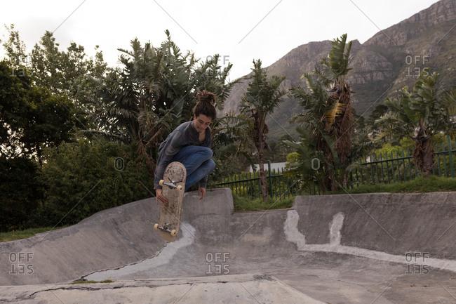 Young man skateboarding at skateboard park