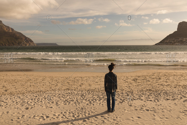Rear view of man standing at beach on a sunny day