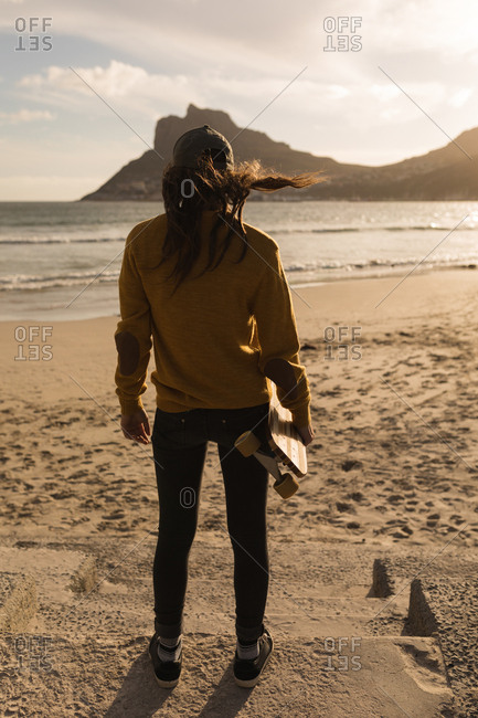 Rear view of woman standing with skateboard on beach