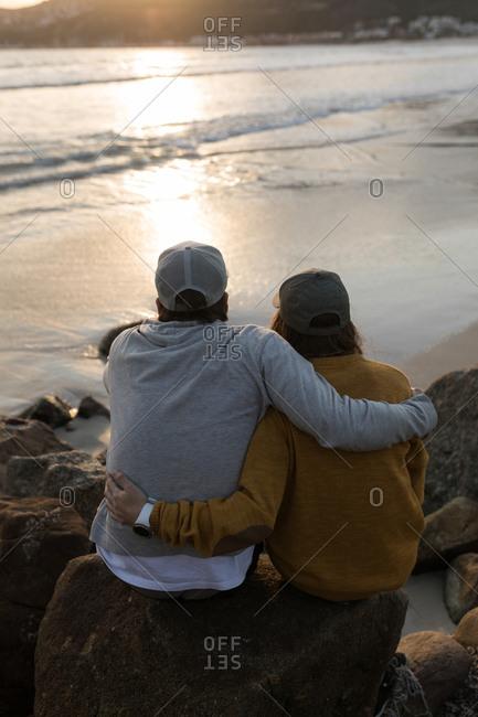 Rear view of couple sitting on rock near beach