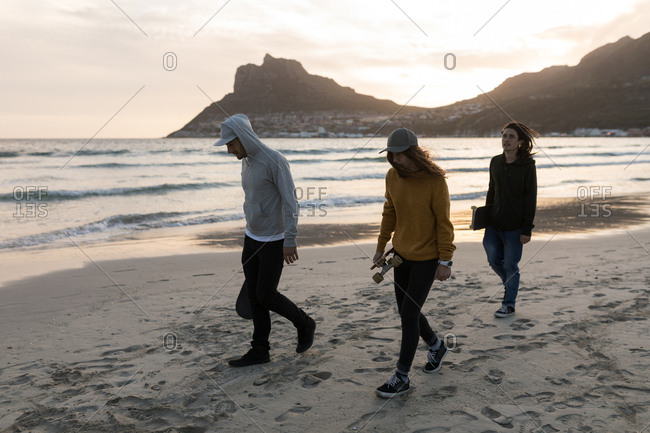 Young skateboarders walking on the beach during sunset