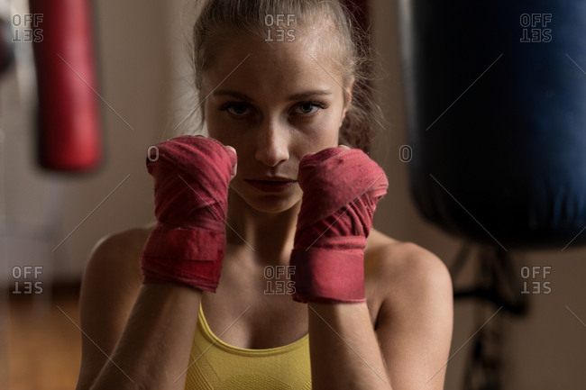 Portrait of female boxer forming hand fist in fitness studio