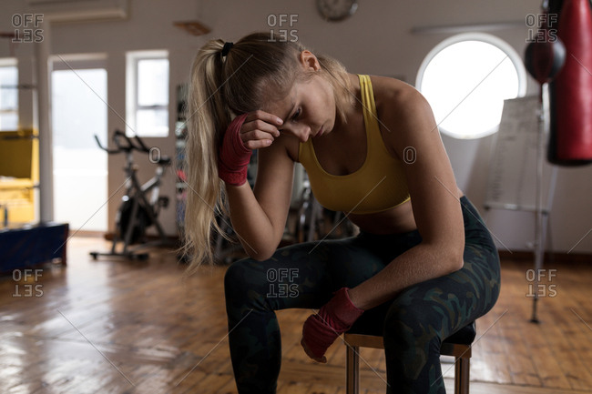 Tired female boxer relaxing in fitness studio