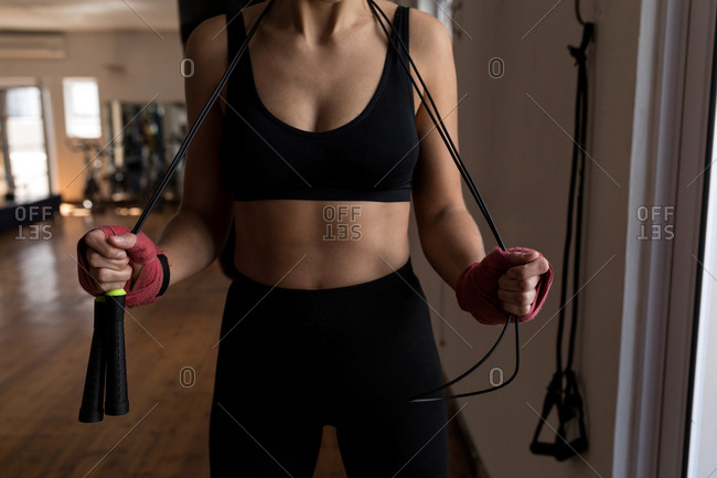 Mid section of female boxer standing with skipping rope in fitness studio