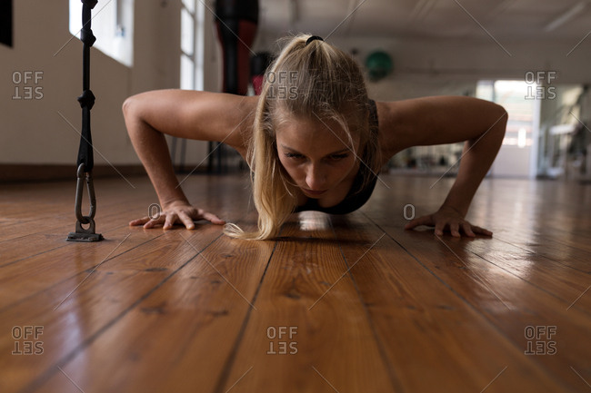 Young female boxer doing push ups in fitness studio