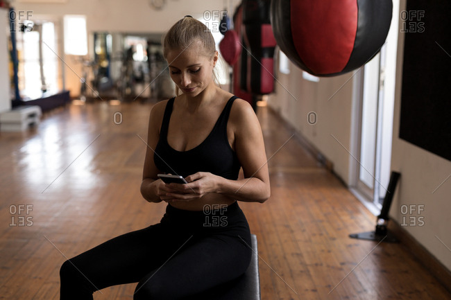 Beautiful female boxer using mobile phone in fitness studio