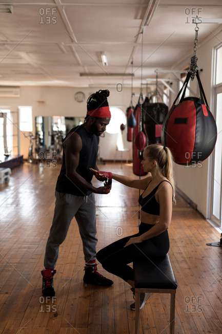 Male trainer assisting female boxer in wearing hand wrap in fitness studio