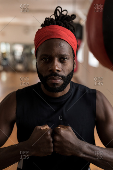 Portrait of male boxer forming hand fist in fitness studio