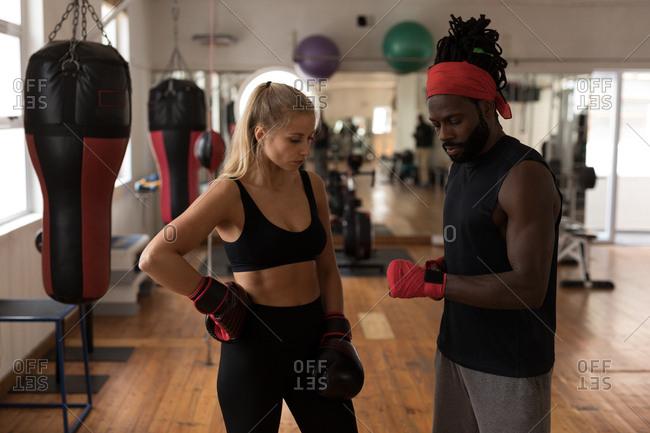 Male trainer assisting female boxer in fitness studio