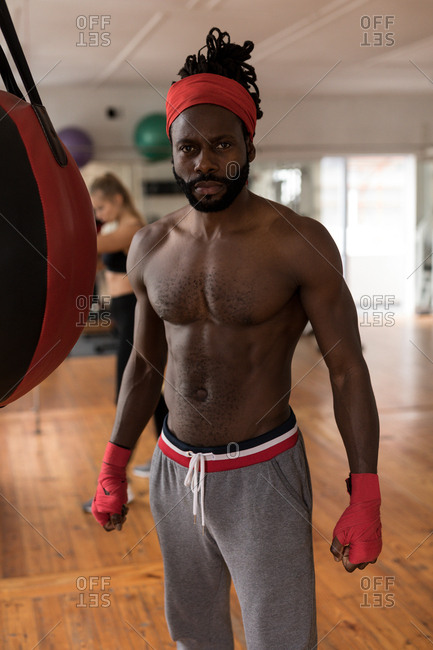 Portrait of shirtless male boxer standing in fitness studio