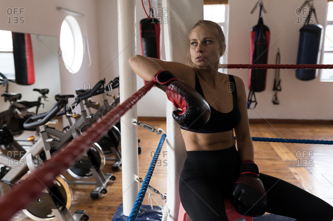 Tired female boxer relaxing in boxing ring at fitness studio