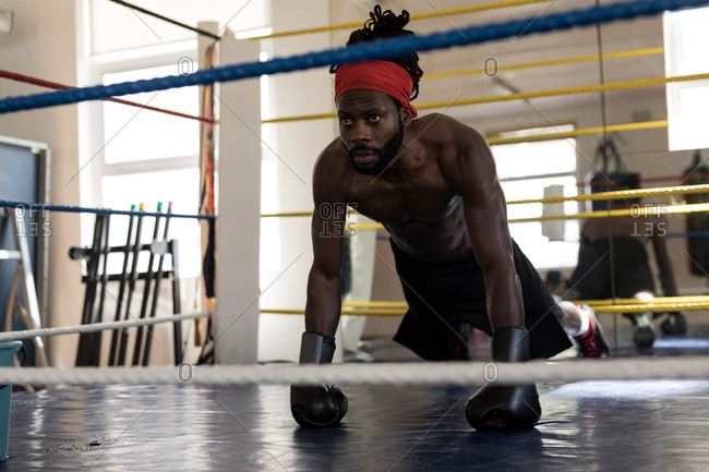 Male boxer doing push ups in boxing ring at fitness studio