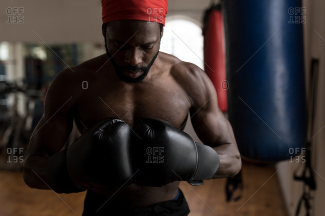 Young male boxer forming hand fist in fitness studio