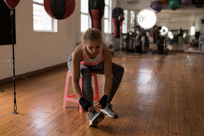Young female boxer tying shoe laces in fitness studio