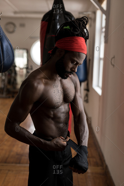 Young male boxer wearing hand wrap in fitness studio