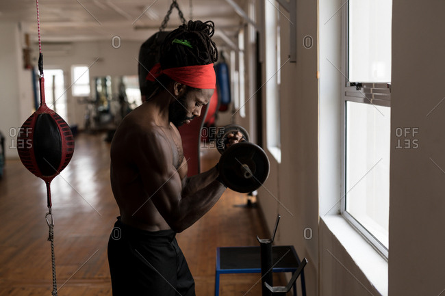 Side view of male boxer exercising with barbell in fitness studio