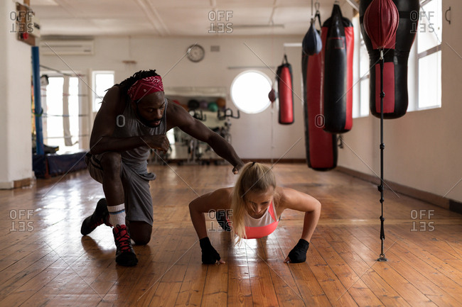 Male trainer assisting female boxer in doing push ups in fitness studio