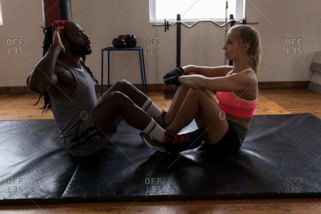 Female trainer assisting male boxer in doing crunches in fitness studio