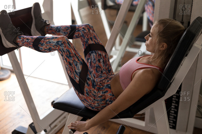 Young female boxer exercising on leg press machine in fitness studio