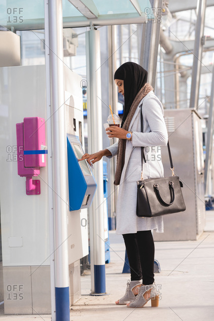 Side view of hijab woman using ticket vending machine at railway station