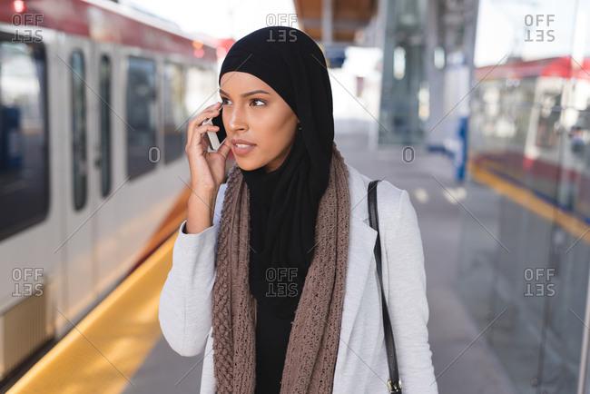 Hijab woman talking on mobile phone in platform at railway station