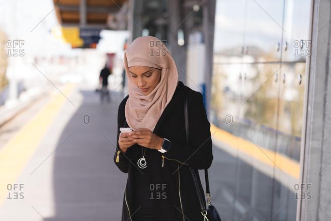 Hijab woman using mobile phone in platform at station