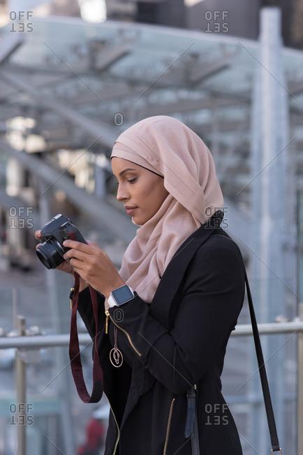Hijab woman reviewing photos in digital camera at balcony