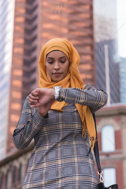 Hijab woman using smart watch in city