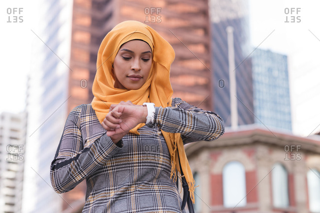 Hijab woman using smart watch in city