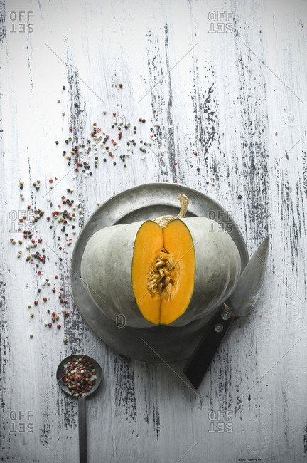 Sliced Cucurbita maxima on tin plate- kitchen knife and peppercorns