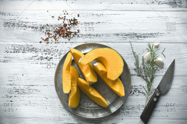 Sliced Cucurbita maxima on tin plate and spices for preparing pumpkin soup