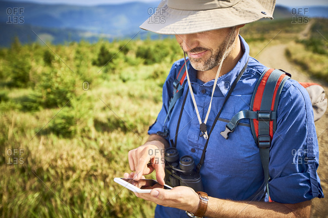 Man checking his cell phone during hiking trip