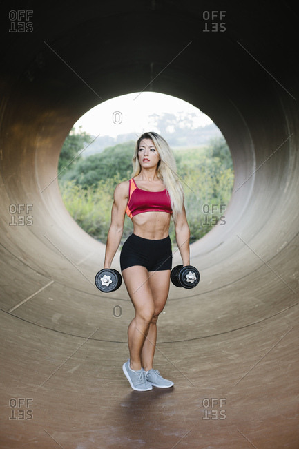 Athletic woman standing inside a tube holding dumbbells
