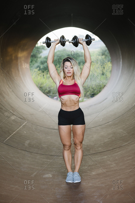 Athletic woman doing weight workout standing inside a tube