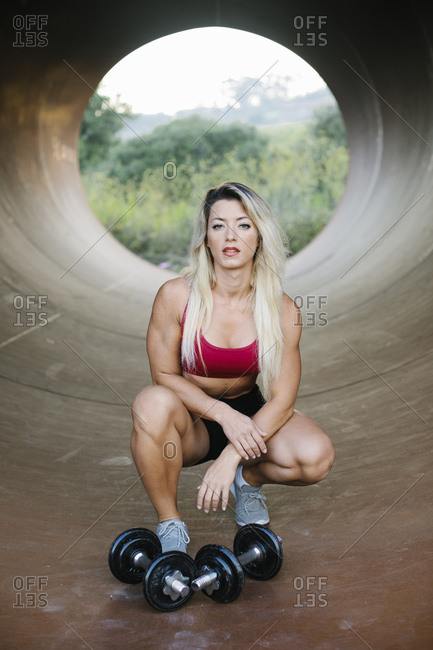 Athletic woman crouching inside a tube with dumbbells