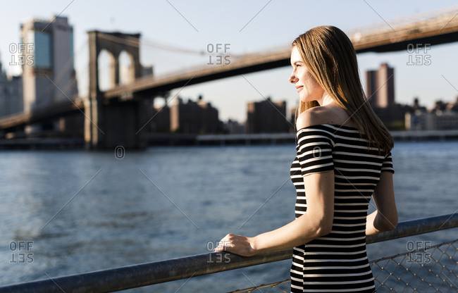 USA- New York- Brooklyn- woman wearing striped dress standing in front of East River by sunset