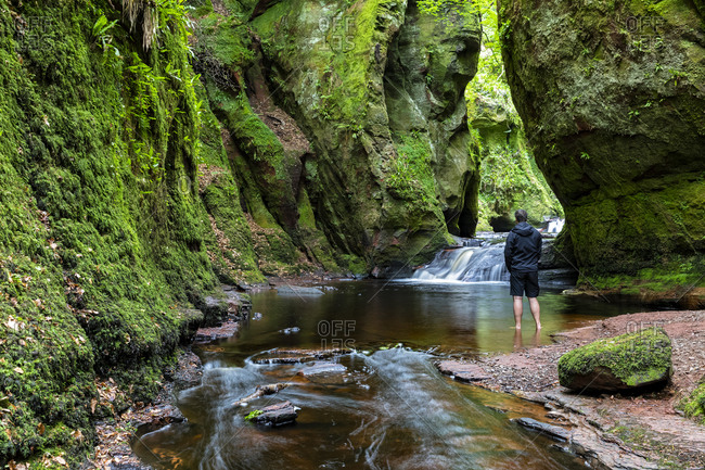 Great Britain- Scotland- Trossachs National Park- Finnich Glen canyon- The Devil's Pulpit- River Carnock Burn- male tourist standing in water