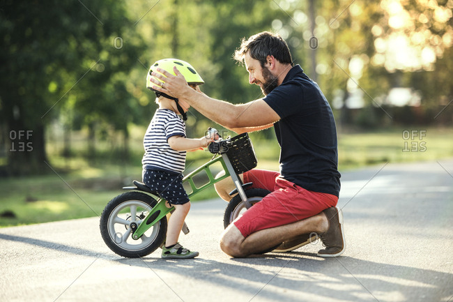 Father supporting little son on bike
