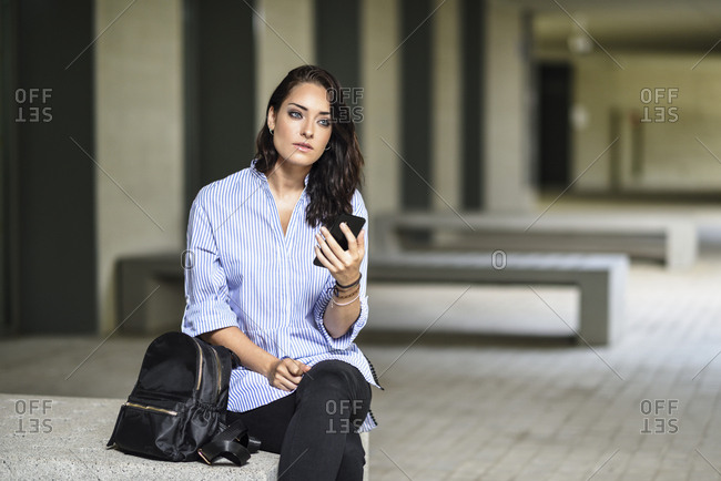 Portrait of pensive student with smartphone on campus