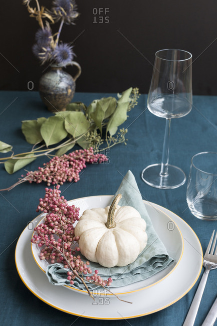 Autumnal table decoration with white decorative gourd and pink peppercorns