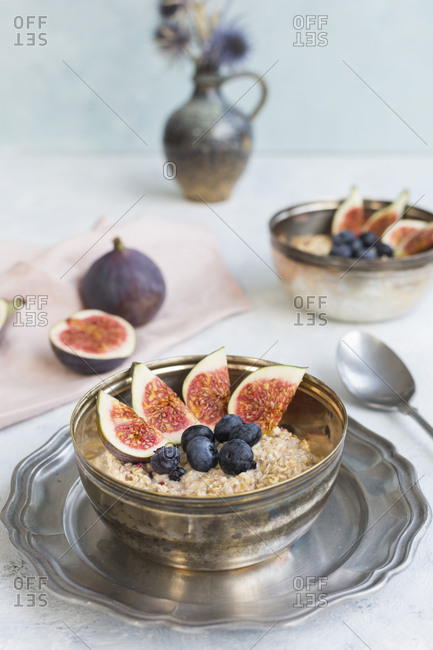 Bowl of porridge with sliced figs- blueberries and dried berries