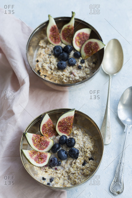 Two bowls of porridge with sliced figs- blueberries and dried berries